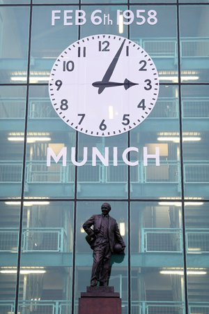 """A picture shows the front of Old Trafford stadium with a clock commemorating the 1958 Munich Air Disaster ahead of the English Premier League football match between Manchester United and Huddersfield Town at Old Trafford in Manchester, north west England, on February 3, 2018. February 6, 2018 at 1504 GMT marks the 60th anniversary of the Munich air disaster that destroyed Manchester United's famed """"Busby Babes"""". The crash killed eight of the United team and three backroom staff, and all but one of the journalists that travelled with the team -- 23 people in all died. Manager Matt Busby was so badly injured he was given the last rites twice. However, he survived and rebuilt the side leading it 10 years on with an epic European Cup victory. / AFP PHOTO / Paul ELLIS / RESTRICTED TO EDITORIAL USE. No use with unauthorized audio, video, data, fixture lists, club/league logos or 'live' services. Online in-match use limited to 75 images, no video emulation. No use in betting, games or single club/league/player publications. /"""